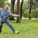 Senior man (60s) exercising in park, practicing tai chi.