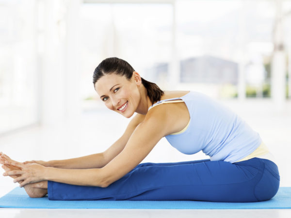 Full length portrait of beautiful young woman performing Seated Forward Bend in yoga class. Horizontal shot.
