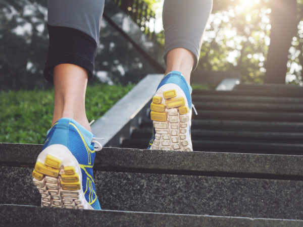 Athlete runner feet running in nature, closeup on shoe. Female athlete running on stairs. Woman fitness, running, jogging, sport, fitness, active lifestyle concept