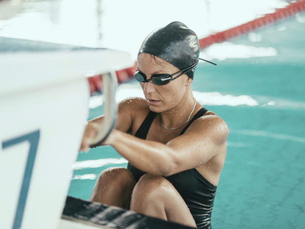 Backstroke swimmer at the swimming block, ready to start the race