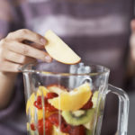 A closeup cropped shot of a woman&#039&#x3B;s hand putting sliced fruits into a blender