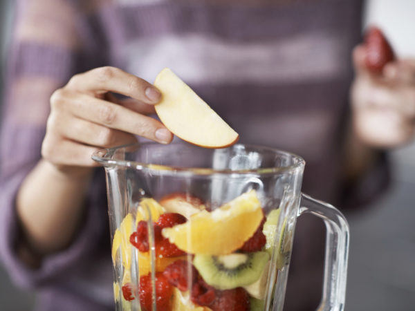 A closeup cropped shot of a woman's hand putting sliced fruits into a blender