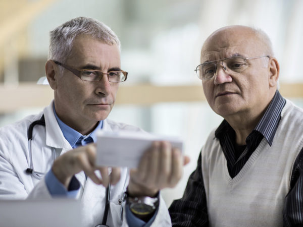 Mature doctor giving an advice to a senior man related to prescription medicine.