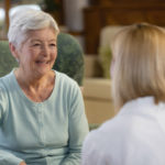 Front view of smiling senior patient sitting in armchair talking with home healthcare nurse or female doctor, rear view.
