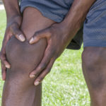 Closeup of knee and leg of lean African American male athlete clutching injured knee with fingers around the patella on green lawn outdoors