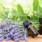essential oils for aromatherapy treatment with herbal flowers using chamomile, lemon balm, and lavender on the wooden table