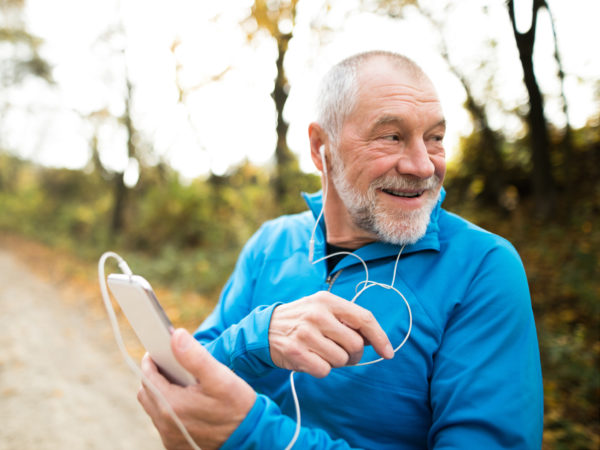 Senior runner in nature. Man with smart phone, listening to classical music.