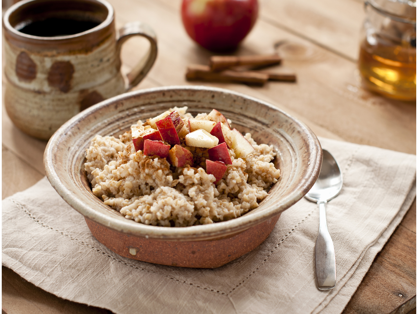 Rustic pottery bowl of steel cut oatmeal with apples, honey, and cinnamon and a cup of coffee.